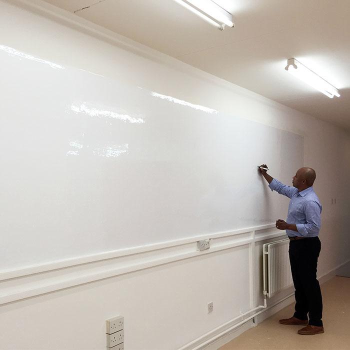 homme qui écrit sur une surface brillante inscriptible créée avec le papier peint tableau blanc