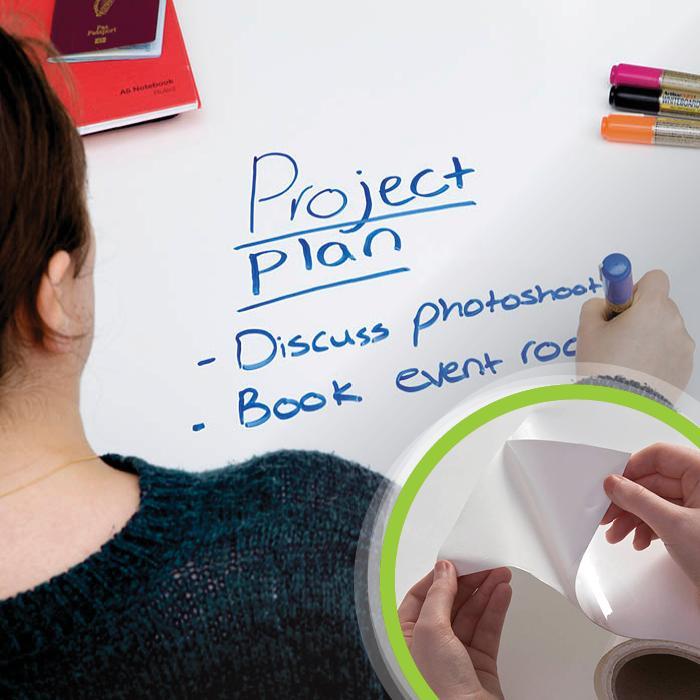 Femme qui écrit sur un bureau avec le film tableau blanc autocollant smart