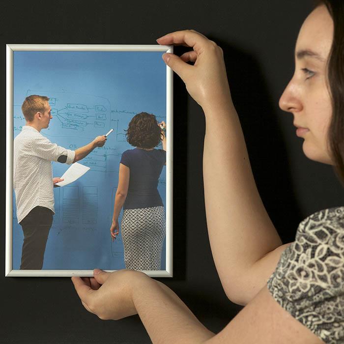 Femme qui accroche un cadre sur un mur peint avec la peinture super magnétique