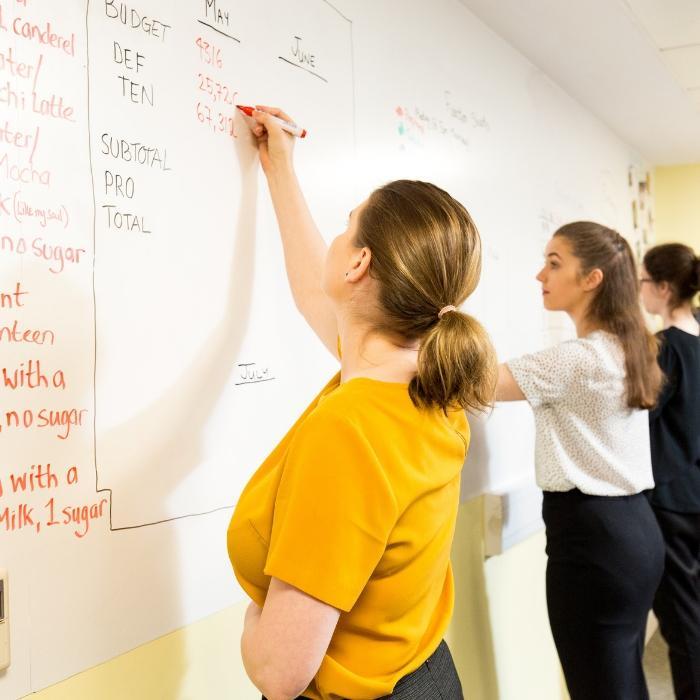 Femmes qui écrivent sur mur avec papier peint magnétique tableau blanc