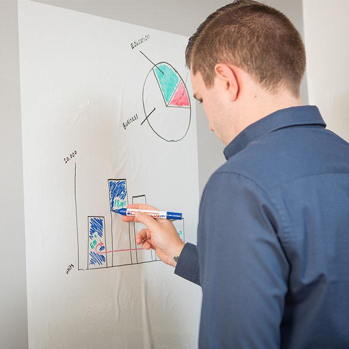 homme utilisant une feuille tableau blanc smart pour dessiner un graphique