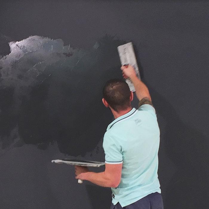 peintre qui installe le plâtre magnétique sur mur