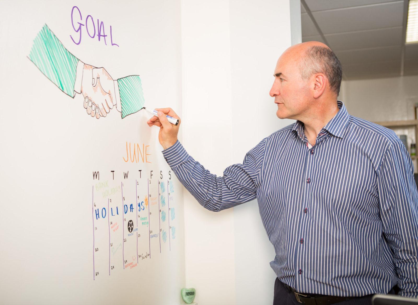 un homme écrit sur le mur du tableau blanc